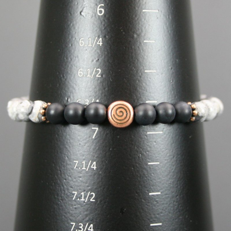 Silver crazy lace agate and matte black onyx stretch bracelet with an antiqued copper spiral focal