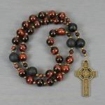 Anglican rosary in red tiger eye and black onyx with a bronze colored Celtic cross