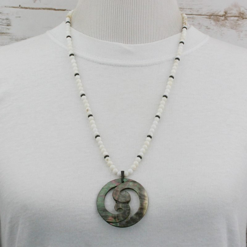 Lip shell double spiral pendant on strand of shell beads