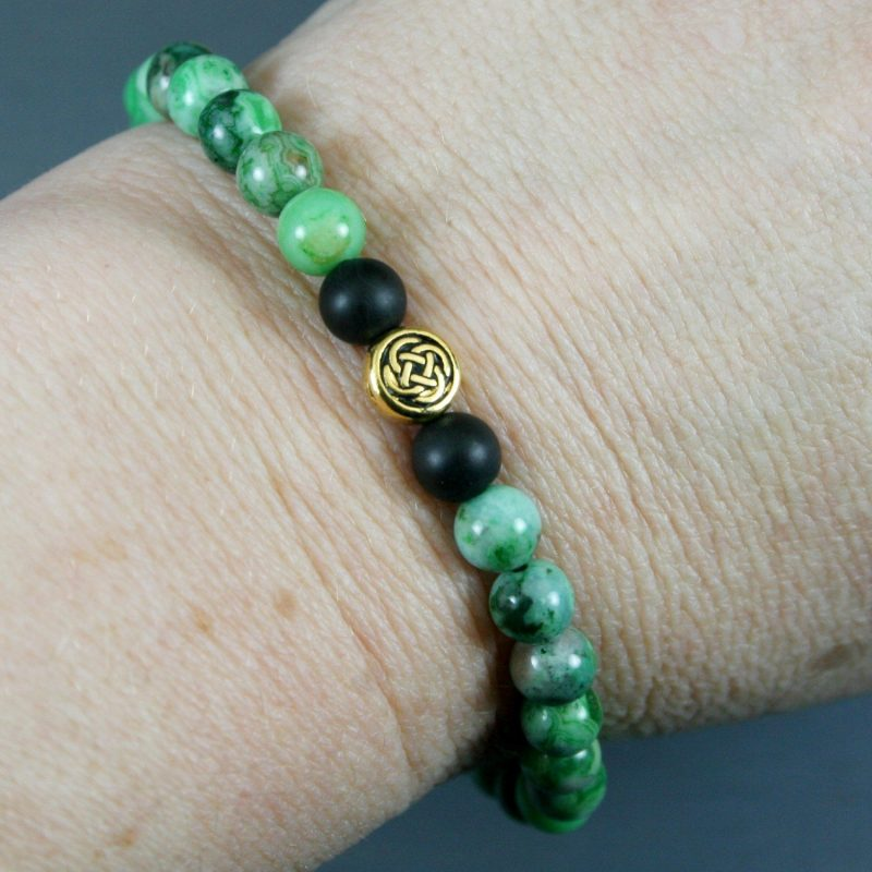 Green crazy lace agate and matte black onyx stretch bracelet with a Celtic knot focal