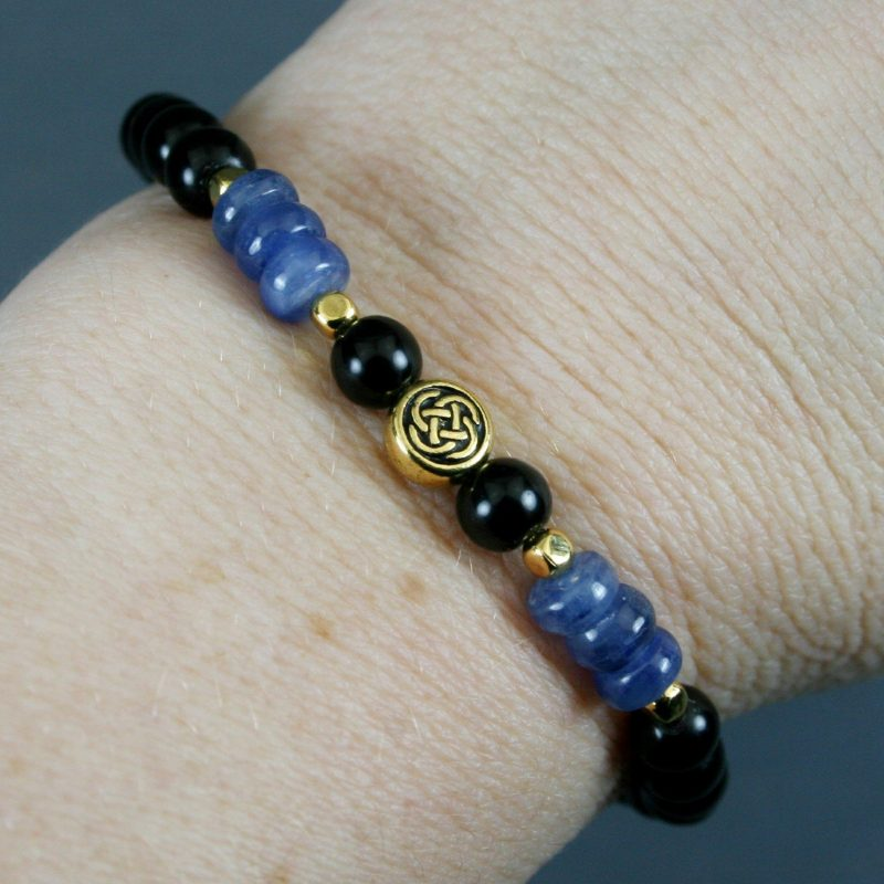 Obsidian and kyanite stretch bracelet with a gold plated Celtic knot focal